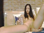 Asian spreading on bed chatting in cellphone.