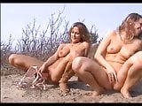 Nude Beach - Two girls share a dildo