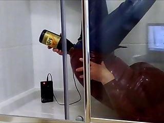 Latex slave gives himself a beer enema...